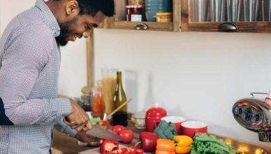 Man cutting peppers in kitchen